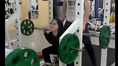 Fit muscled teen screaming from pain doing last set of heavy squats loop