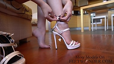 Sexy girls shows her feet and legs on high heels, trying different pairs