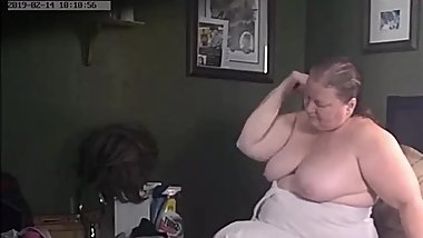 Ugly wife sits on the bed topless combing her hair